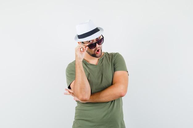 緑のtシャツと帽子の眼鏡を見て好奇心旺盛な若い男性