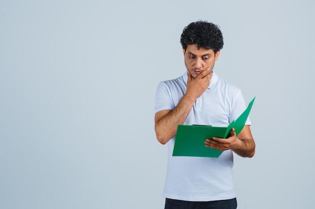 白いtシャツ、ズボン、物思いにふける、正面図でクリップボードのメモを見ている若い男性。