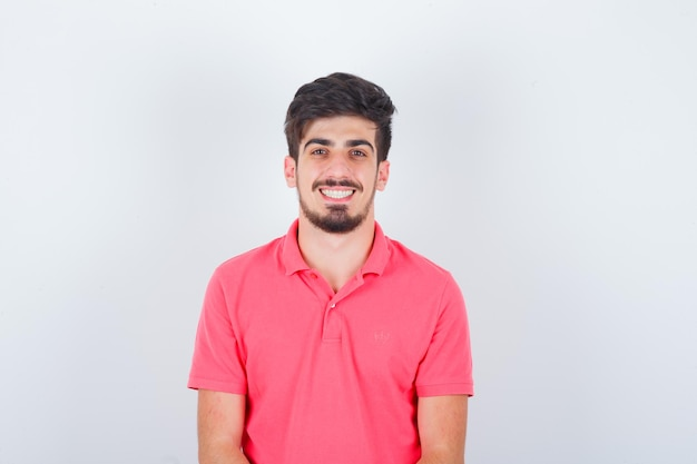 Young male looking in pink t-shirt and looking cheerful , front view.