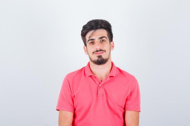 Giovane maschio che guarda in maglietta rosa e sembra sensato, vista frontale.