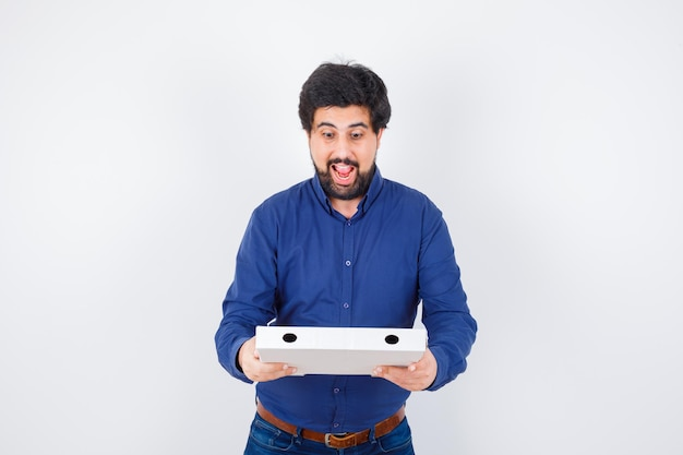 Young male looking at pizza box in shirt, jeans and looking joyful. front view.