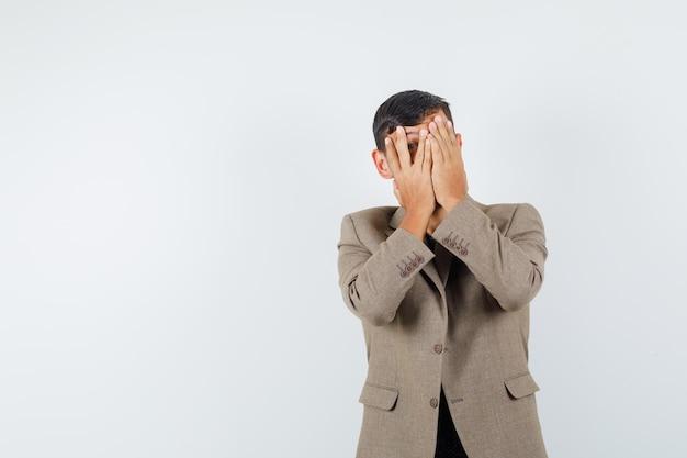 Giovane maschio che guarda attraverso le dita in giacca marrone grigiastra e sembra spaventato. vista frontale. spazio per il testo
