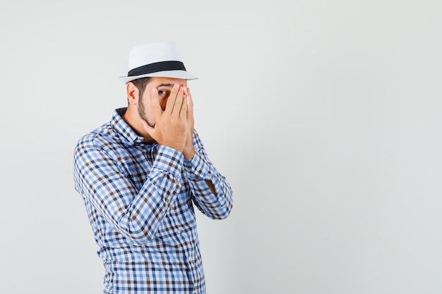 チェックシャツ、帽子、怖い顔、正面図で指を通して見ている若い男性。