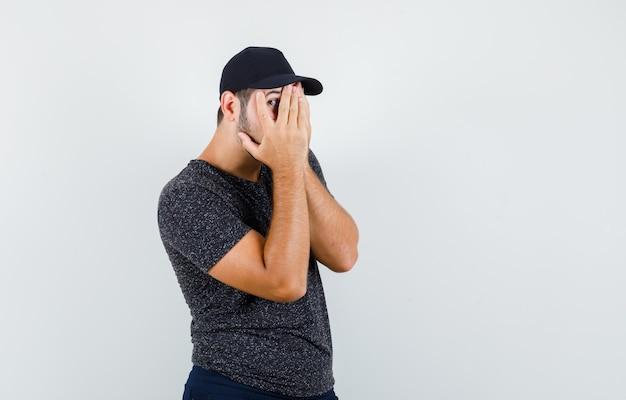 Молодой мужчина смотрит сквозь пальцы в футболке и кепке, джинсах и с любопытством смотрит