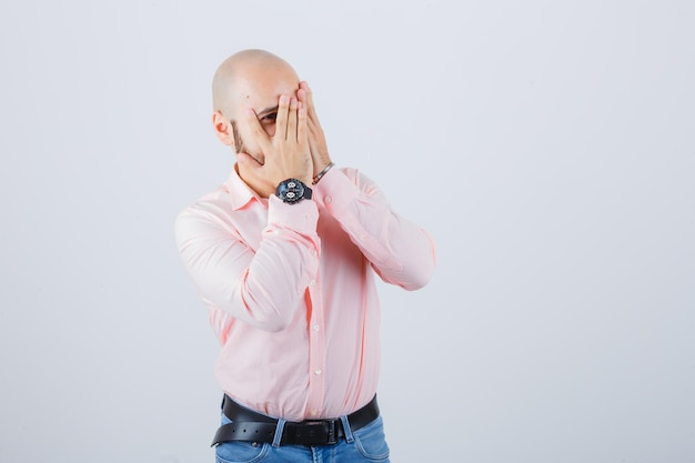 Giovane maschio guardando attraverso le dita un occhio in camicia, jeans e guardando carino, vista frontale.