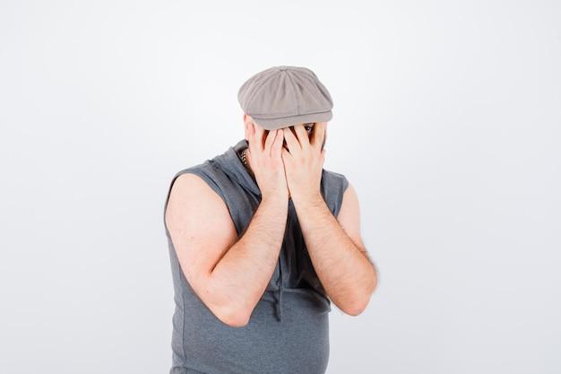 Giovane maschio che guarda attraverso le dita con un occhio in felpa con cappuccio senza maniche, berretto e sembra carino, vista frontale.