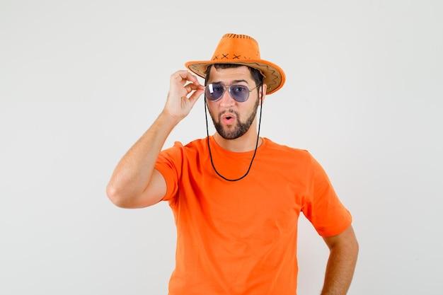주황색 티셔츠, 모자를 쓰고 멋진 안경을 쓴 젊은 남성. 전면보기.