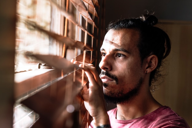 A young male looking through the window blinds to stay safe during coronavirus outbreak