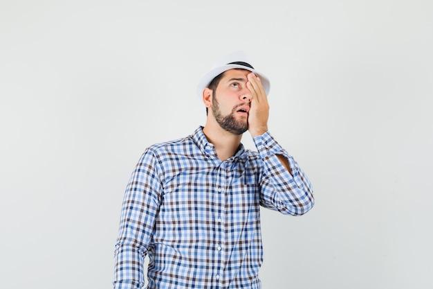 Giovane maschio che osserva in su con la mano sull'occhio in camicia controllata, cappello e sguardo ansioso. vista frontale.