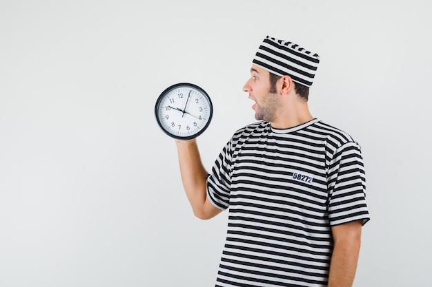 Giovane maschio guardando l'orologio da parete in t-shirt, cappello e guardando sorpreso, vista frontale.