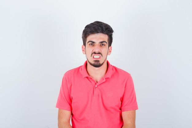 Молодой мужчина смотрит со стиснутыми зубами в розовой футболке и выглядит сердитым, вид спереди.