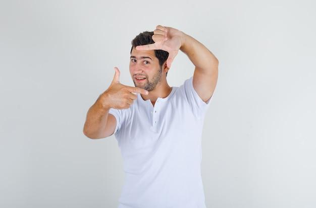 白いtシャツでフレームジェスチャーを作ると幸せそうに見えて若い男性