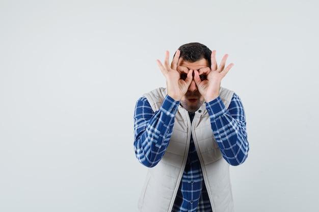Молодой мужчина делает очки жестом на его глазах в рубашке, куртке без рукавов и выглядит удивленным. передний план.
