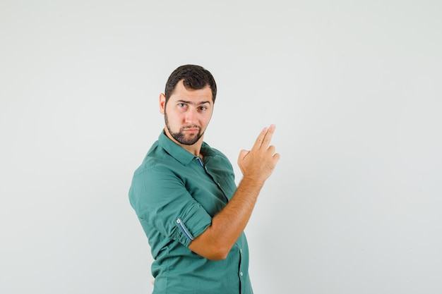 Young male making pistol gesture in green shirt and looking serious. front view.