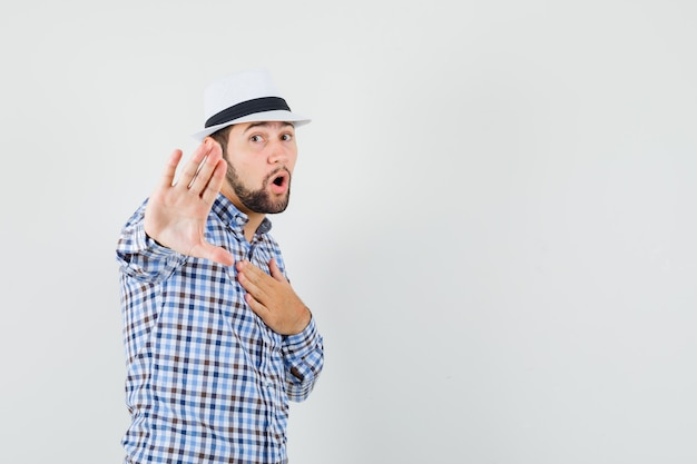 Young male making refusal gesture by pointing at himself in checked shirt, hat and looking scared. front view.