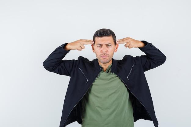 若い男性がtシャツ、ジャケットで自殺ジェスチャーをし、落ち込んでいるように見えます。正面図。