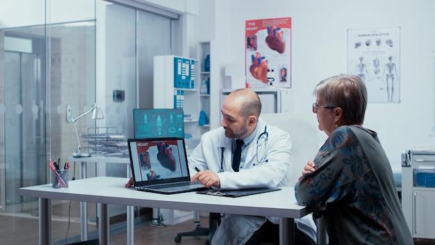 Молодой мужчина-медик, представляя брошюру о сердце на пк пожилой пенсионерке. проблемы с пороком сердца, представленные кардиологом-кардиологом, прикрепляют к сердцу. здравоохранение в современной частной клинике