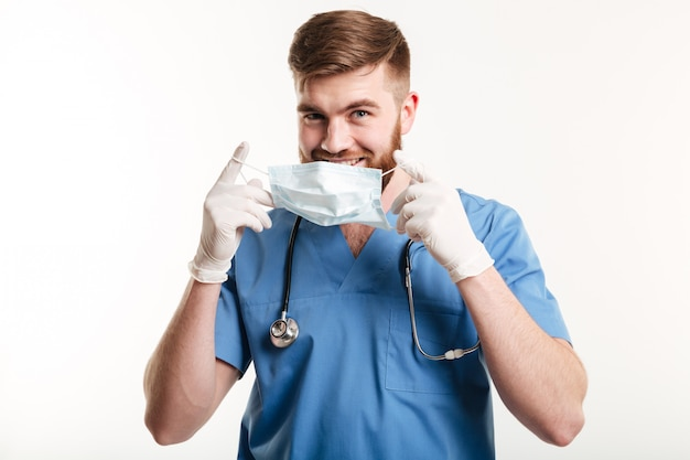 Young male medical doctor or nurse putting sterile mask