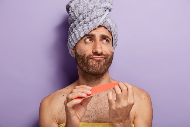 Young male model does manicure with nail file, wears silicone patches under eyes, has beauty treatments, wears towel on head, stands with bare torso against purple wall, looks aside pensively