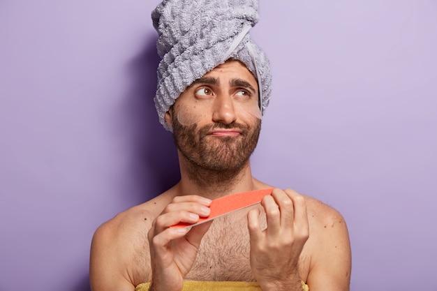 Il giovane modello maschio fa manicure con lima per unghie, indossa cerotti in silicone sotto gli occhi, ha trattamenti di bellezza, indossa un asciugamano sulla testa, sta con il torso nudo contro il muro viola, guarda pensieroso