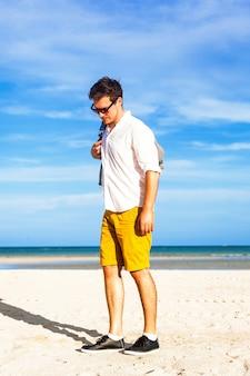 세련된 배낭과 함께 바다로 여름 휴가를 즐기는 젊은 남성 모델