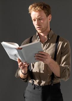 Молодая модель мужского пола, читающая книгу