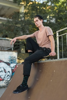 Young male model sitting on skateboard