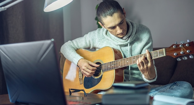 Young male musician is learning to play acoustic guitar in an online lesson using laptop