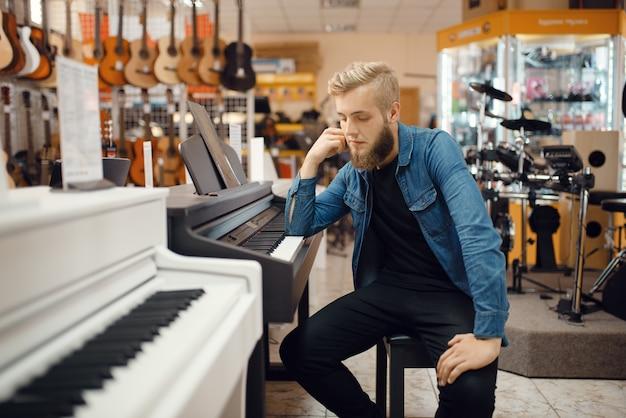 젊은 남성 음악가는 뮤직 스토어에서 피아노에 포즈. 악기 상점의 구색, 장비 구입 키보드 연주자, 시장의 피아니스트