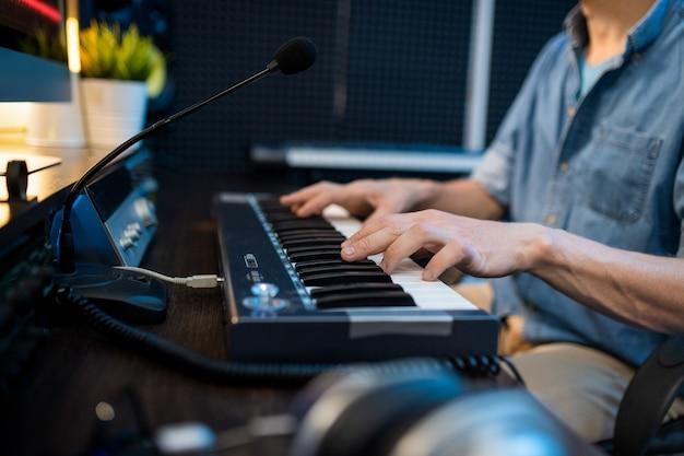 Молодой мужчина-музыкант трогает клавиши фортепианной клавиатуры, сидя на рабочем месте и записывая новую музыку