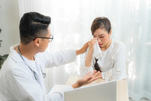 若い男性の産婦人科医-クリニックまたは病院で患者と相談している婦人科医。