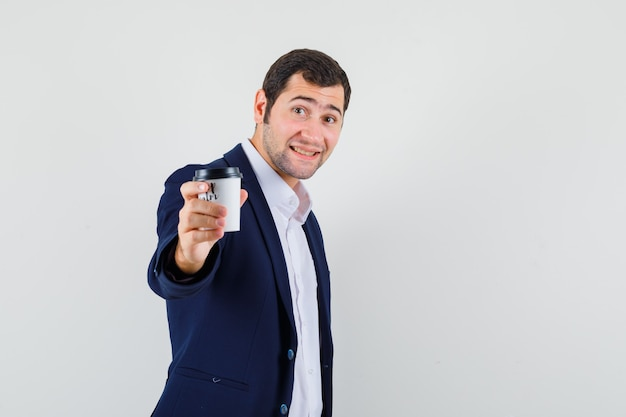 Giovane maschio che offre tazza di caffè in camicia e giacca e sembra gentile