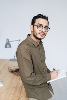 Young male office worker in casualwear and eyeglasses looking at you while thinking of ideas and writing them down in notebook