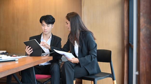 사무실에 앉아서 동료와 함께 일하는 휠체어를 탄 젊은 남성 회사원.
