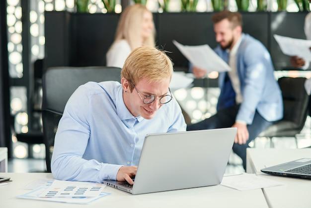 좋은 미소와 함께 재미있는 안경에 젊은 남성 회사원 그의 직장 및 동료 배경에 노트북을 사용 하여 앉는 다.