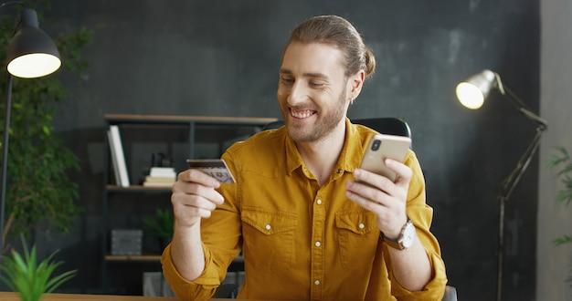 テーブルに座って、クレジットカードを保持し、ラップトップコンピューターでオンラインショッピングを行う若い男性会社員。