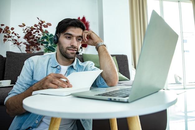 Молодой мужчина на своем ноутбуке, оператор телефонного центра разговаривает с клиентами через наушники