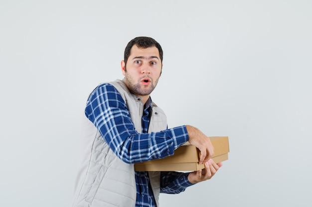 シャツ、ジャケット、興奮して見える若い男性のオープニングボックス。正面図。