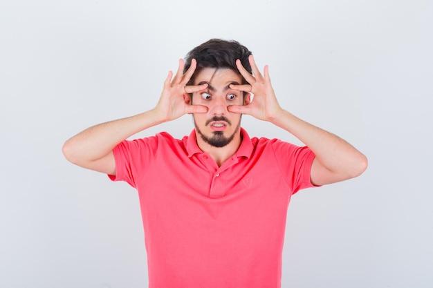 Молодой мужчина открывает глаза руками в розовой футболке и выглядит встревоженным. передний план.