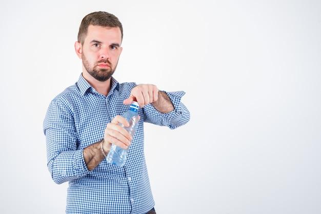 Giovane maschio apertura bottiglia d'acqua in plastica in camicia, jeans e guardando fiducioso, vista frontale.