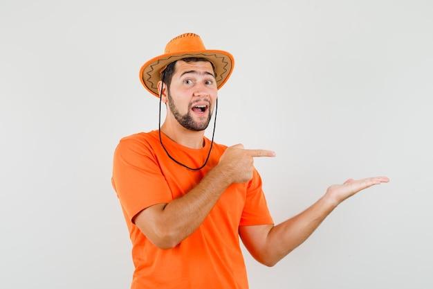 Giovane maschio in maglietta arancione, cappello che punta al palmo aperto da parte, vista frontale.