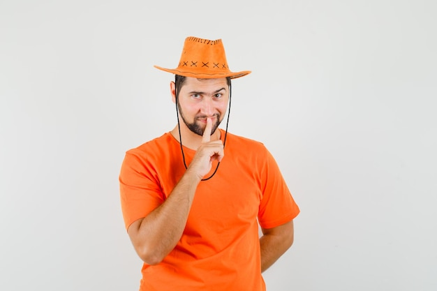 Giovane maschio in maglietta arancione, cappello che mostra gesto di silenzio e sguardo astuto, vista frontale.