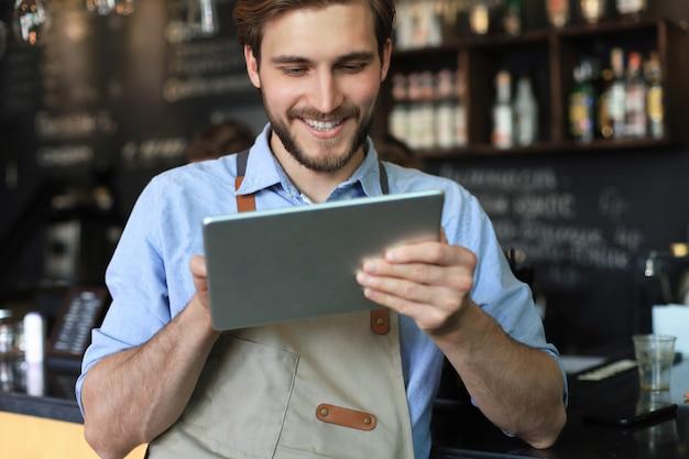 Молодой мужчина-владелец с помощью цифрового планшета, стоя в кафе.