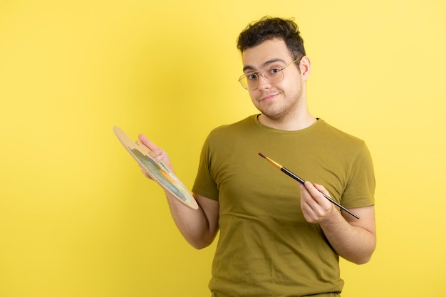 Young male painter with painting palette and brush.
