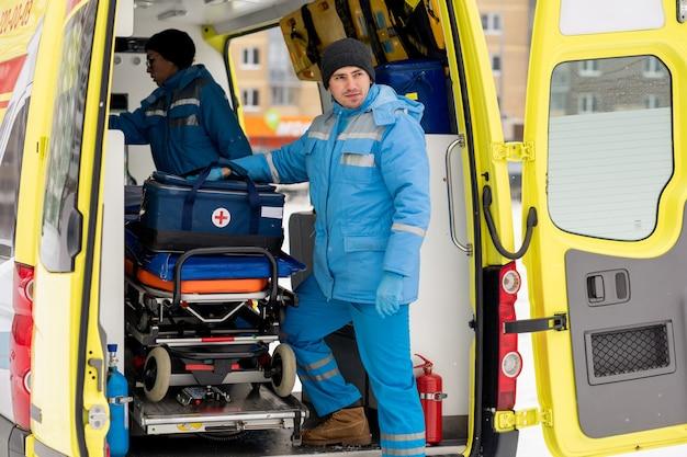 救急車のドアの担架のそばに立ってまっすぐ見ている救急箱を持った若い男性救急隊員