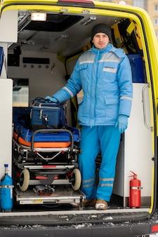 Молодой мужчина-фельдшер с аптечкой стоит на носилках в машине скорой помощи