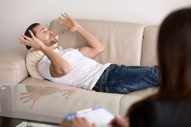 Young male patient lying on couch talking to female psychologist