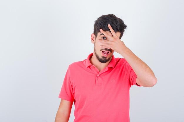片目でtシャツを着て覗き込んでいる若い男性がかわいく見える正面図。