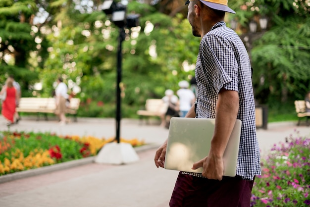 A young male person carrying the laptop in the city