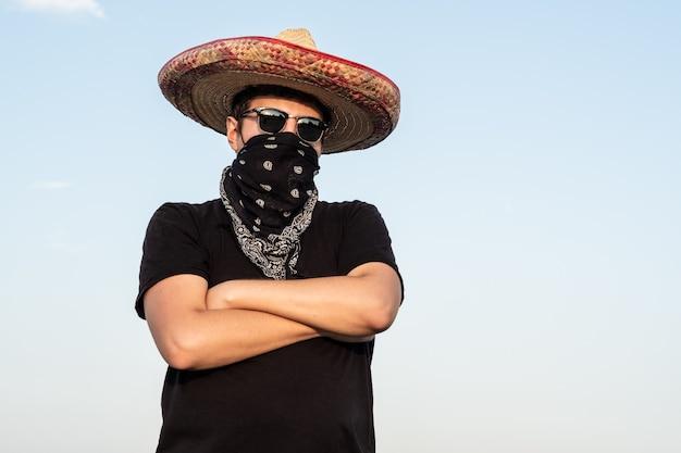 Молодой человек мужского пола одет как гангстер в традиционном сомбреро, бандане. мексиканский праздник или концепция хэллоуина человека, изображающего бандита или бандита в западном стиле